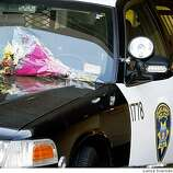 Flowers lay on an Oakland Police car outside Fry Family Chapel in Tracy California site of a small ceremony for Oakland Police Sgt Mark Dunakin one of four officers killed in the line of duty last week.  Friday, March 27, 2009.