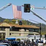 An American flag strung between two fire department ladder trucks greets mourners in the funeral procession for Oakland, Calif., Police Officer Ervin Romans as it turns from Hartz Avenue onto Diablo Road in Danville, Calif., on Friday, Mar. 27, 2009. The procession is enroute to a memorial service in Oakland for Romans and two other officers who were killed in the line of duty in Oakland on Saturday, Mar. 21.