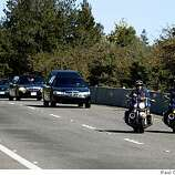 The funeral procession for police officer John Hege heads down Highway 13 to the memorial service at Oracle Arena in Oakland, Calif., on Friday, March 27, 2009.