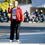 Bill Kaska a retired Fremont Fireman records the funeral procession for Oakland Police Sgt Mark Dunakin as it passes in Tracy California Friday, March 27, 2009. Dunakin was killed in the line of duty with three other officers last week.