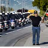 Tim Durbin a retired Alameda Sheriff Sergeant who once worked with officer Dunakin pays his last respects to the fallen Oakland Police Sgt as his funeral procession passes in Tracy California. Dunakin was shot to death with three other officers in the line of duty last week. Friday, March 27, 2009.