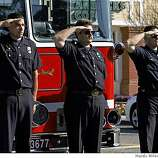 Aaron Goins, Bob Reichmuth, and Captain Sean Chew, from left, of the Hayward Fire Department, stand at attention as the funeral procession for Oakland police officer Dan Sakai goes down Industrial Boulevard in Hayward, Calif., on Friday, March 27, 2009. Sakai was killed along with three other Oakland police officers.