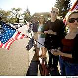 Lea Castleberry of Contra Costa Supervisor Mary Piepho's office (right, holding flag) and coworkers Gina Ferretti (wearing white dress) and Karyn Cornell watch as the funeral procession for Oakland, Calif., Police Officer Ervin Romans travels  on Diablo Road in Danville, Calif., on Friday, Mar. 27, 2009. The procession is enroute to a memorial service in Oakland for Romans and two other officers who were killed in the line of duty in Oakland on Saturday, Mar. 21.