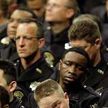 Oakland police officers react during the eulogies for the fallen officers, during public memorial service at the Oracle Arena in Oakland, Calif. on Friday March 27, 2009, for the 4 police officers killed by a gunman last Saturday near the corner of 74th Ave. and MacArthur Blvd.
