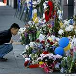 Randy Tran stops to view the memorial in front of Oakland Police headquarters which was closed for business during the funeral service for four slain officers in Oakland, Calif., on Friday, March 27, 2009.