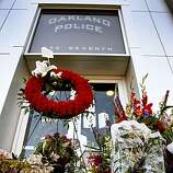 A memorial for the four slain officers blocks an entrance to Oakland Police headquarters which was closed for business during the funeral service in Oakland, Calif., on Friday, March 27, 2009.