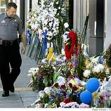 Sheriff's Sgt. Ray Kelly walks past a memorial in front Oakland Police headquarters which was closed for business during the funeral service for four slain officers in Oakland, Calif., on Friday, March 27, 2009. Kelly, normally a detective with the Alameda County Sheriff's Department, was patrolling the streets of Oakland while the entire Oakland police force attended the funeral.