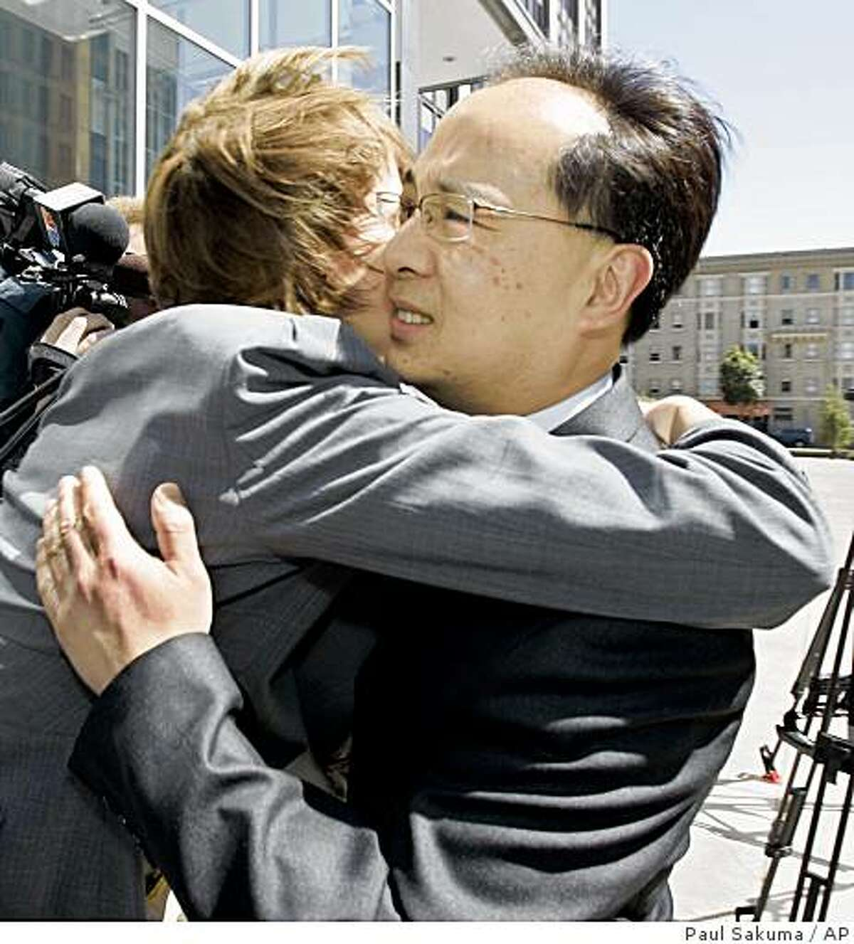 Former San Francisco Supervisor Ed Jew, right, gets a hug from a supporter after a sentencing hearing at a federal courthouse in San Francisco, Friday, April 3, 2009. Jew has been sentenced to five years and four months in prison for attempting to shake down small city businesses having planning permit problems. He was ensnared in a 2007 FBI sting that videotaped Jew receiving $40,000 in marked bills from an owner of a Quickly fast-food restaurant. He later pleaded guilty to one count each of bribery, extortion and fraud and admitted he tried to force several Quickly owners to pay him a combined $80,000. (AP Photo/Paul Sakuma)