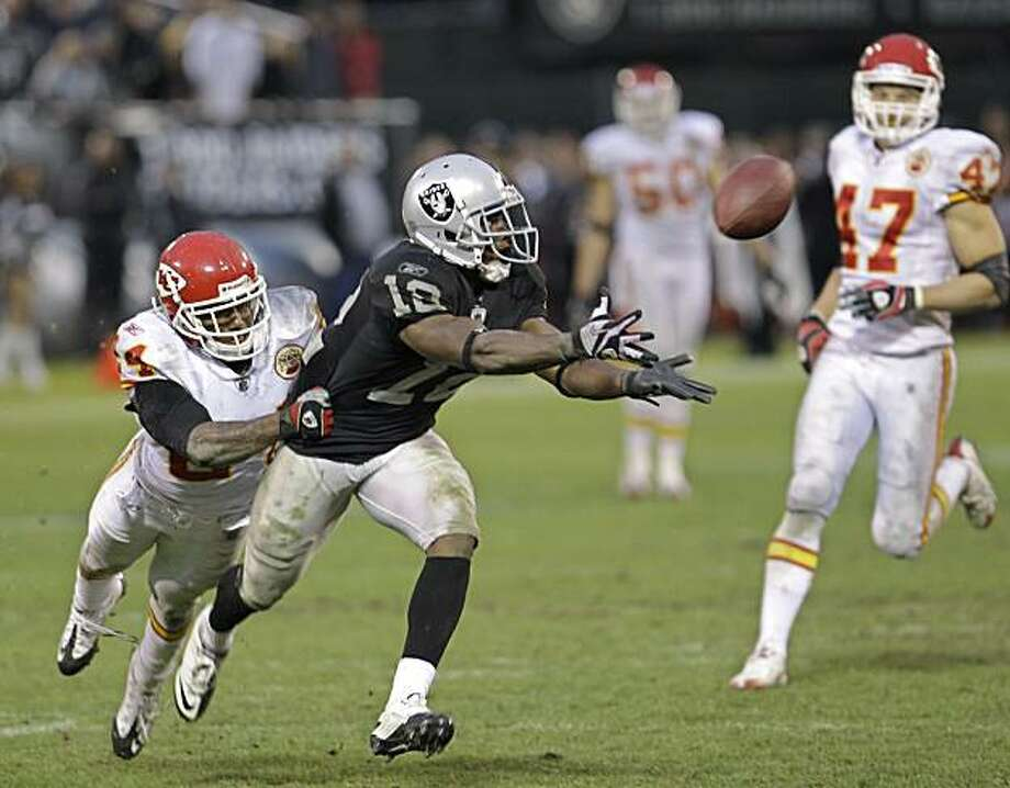 Oakland Raiders wide receiver Jacoby Ford (12) catches a 47 yard pass in front of Kansas City Chiefs cornerback Brandon Flowers (24) to help set up a field in overtime for the Raiders to defeat the Chiefs 23-20 in an NFL football game in Oakland, Calif.,Sunday, Nov. 7, 2010. Photo: Paul Sakuma, AP