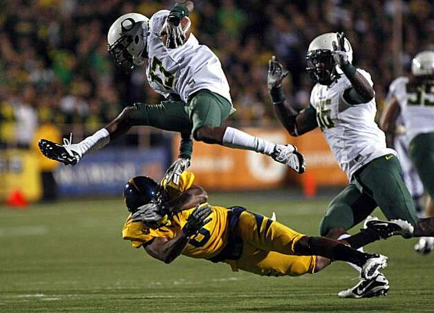 Cal's C.J. Montgomery cuts under the Ducks' Cliff Harris, who fumbled on a third quarter kickoff return Saturday at Memorial Stadium in Berkeley. Photo: Lance Iversen, The Chronicle