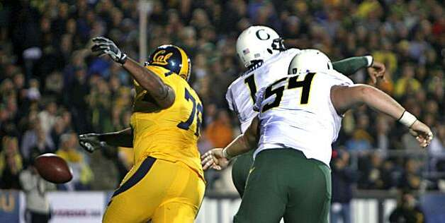 Cal's Derrick Hill knocks the ball out of Ducks quarterback Darron Thomas' hand Saturday at Memorial Stadium. Hill fell on the ball in the end zone for a Cal touchdown. Photo: Lance Iversen, The Chronicle