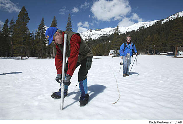 Frank Gehrke,  left, chief of snow surveys for the Department of Water Resources, pulls a snowpack survey tube out of the snow as DWR's Kenny Karcher, right, looks on during the snow survey near Echo Summit, Calif., April 2, 2009.  The survey showed the snow pack to to be 48.7 inches deep, with a water content of 22.6 inches which is about 80 percent of normal at this location for this time of the year.(AP Photo/Rich Pedroncelli) Photo: Rich Pedroncelli, AP