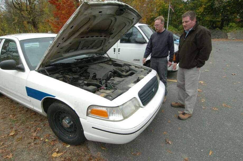 From left, Bob Keane and Tim Nolan, of Danbury Public Works, talks about cars that were recently serviced for auction. Images taken Friday, Oct. 30, 2009. Photo: Chris Ware / The News-Times