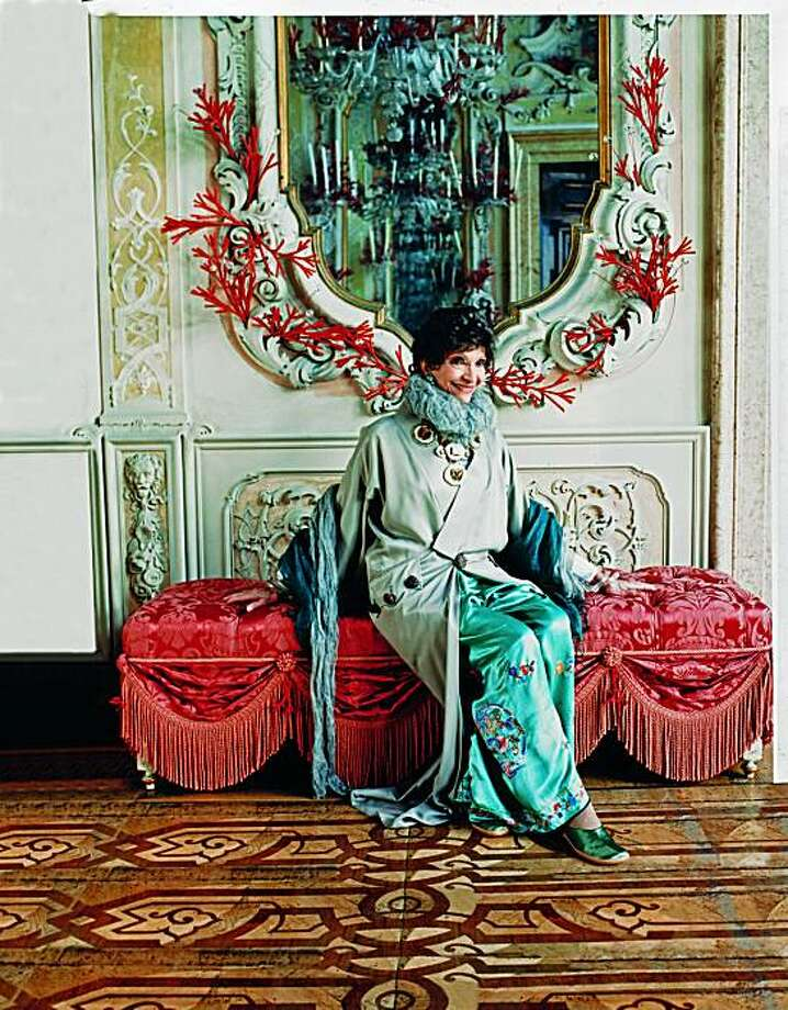 """International hostess and fashionista Dodie Rosekrans and her late husband, John Rosekrans, had the late interior designer Tony Duquette and his design partner, Hutton Wilkinson, transform a palazzo on Venice, Italy's Grand Canal into a fantasy palace. Here, Dodie sits under a mirror adorned with coral """"antlers"""" in the ballroom. She is wearing Galliano haute couture. The home is featured in the new book, """"At Home with Town & Country,"""" (Hearst Books, 2010.) Reprinted with permission from At Home with Town & Country, copyright 2010 by Hearst Books, a division of Sterling Publishing Co., Inc."""" Photo: Tk"""