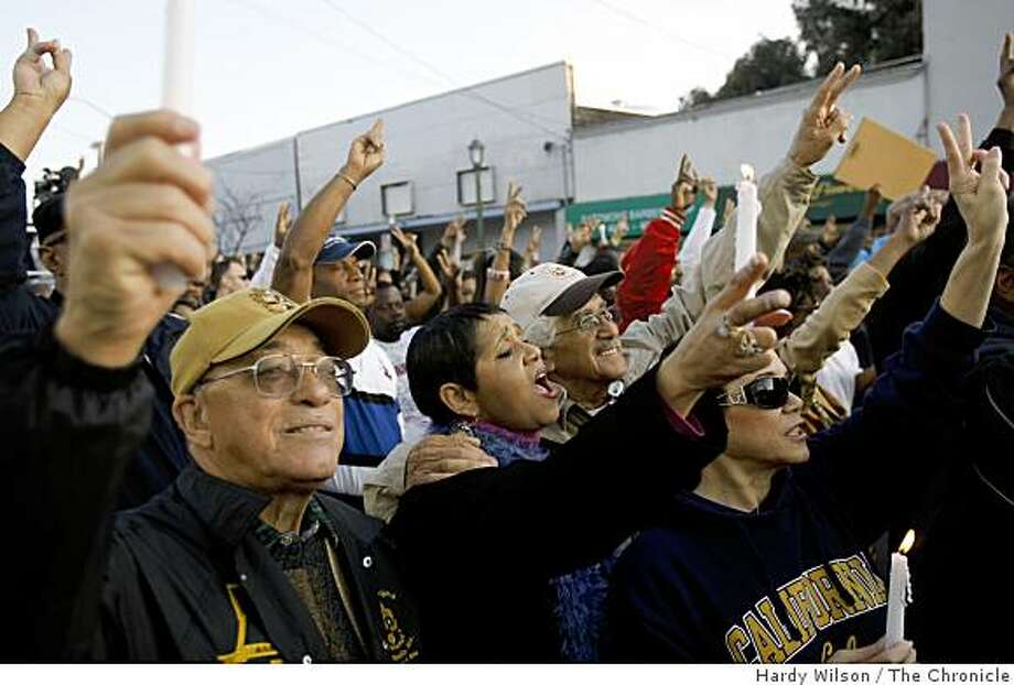 """Family members (l-r) Nat Barner, Kathy Britton, Freddie Martin, and Michelle Martin, all of Oakland, raise up a """"peace"""" sign during a vigil at MacArthur and 74th Avenue in Oakland, Calif., for the four killed police officers on Tuesday, March 24, 2009. Photo: Hardy Wilson, The Chronicle"""