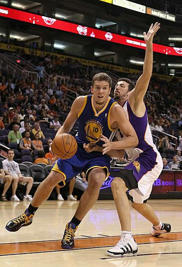 PHOENIX - OCTOBER 19:  David Lee #10 of the Golden State Warriors handles the ball under pressure from Hedo Turkoglu #19 of the Phoenix Suns during the preseason NBA game at US Airways Center on October 19, 2010 in Phoenix, Arizona. NOTE TO USER: User expressly acknowledges and agrees that, by downloading and or using this photograph, User is consenting to the terms and conditions of the Getty Images License Agreement. Photo: Christian Petersen, Getty Images