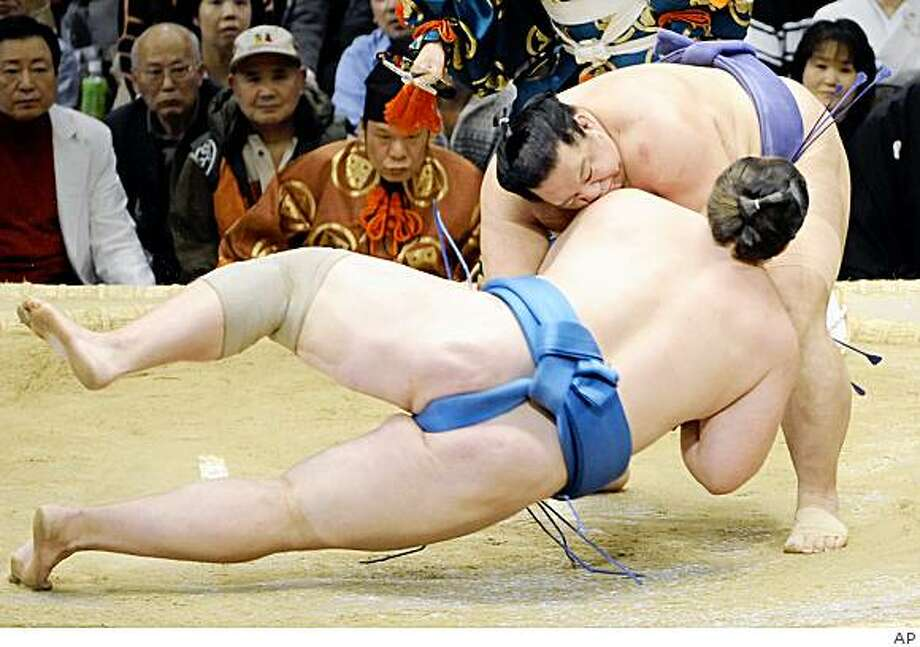 Sumo wrestler Baruto, back to camera, is hurled down to the dirt by champion Kaio during their bout at Osaka, western Japan, on Wednesday March 18, 2009. Baruto, who hails from Estonia, suffered his second straight loss, dropping to 2-2 after Day Four of the Spring Grand Sumo Tournament. Kaio now is 3-1. (AP Photo/Kyodo News) ** JAPAN OUT, MANDATORY CREDIT, FOR COMMERCIAL USE ONLY IN NORTH AMERICA ** Photo: AP