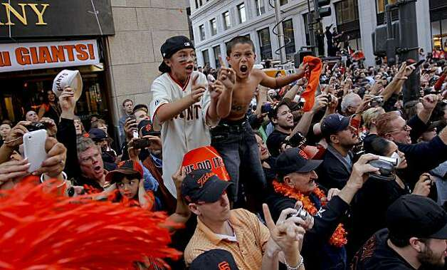 Emilee Pineda, (left) and Lucky Fenton, of San Francisco,  got a different kind of lesson today while cheering the Giants along the parade route, as the City of San Francisco celebrates the World Series Champion Giants with a parade down Market Street, on Wednesday Nov. 3, 2010 in San Francisco, Calif. Photo: Michael Macor, San Francisco Chronicle