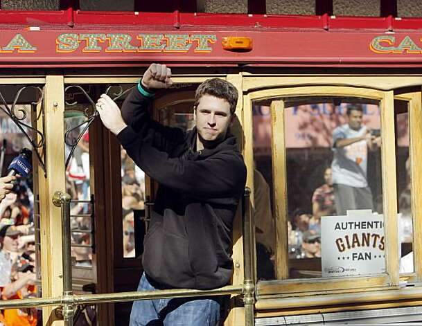 Buster Posey pumps his fist to the crowd gathered during the parade. The city of San Francisco held a victory parade for the World Champion San Francisco Giants on Wednesday, November 3, 2010, two days after the team won the World Series against the Texas Rangers. The parade came down Market Street in San Francisco, Calif., and was the same route taken by the parade welcoming the Giants to San Francisco in 1958 when they moved from New York to the west coast. Photo: Carlos Avila Gonzalez, San Francisco Chronicle