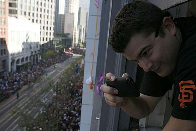 Johnny Faustine takes a video from the fifth floor of the Hearst Building off Market St. in San Francisco, Calif. to watch the San Francisco Giants' World Series parade at their home city in San Francisco, Calif. on Wednesday, Nov, 3, 2010. Photo: Kirsten Aguilar, The Chronicle