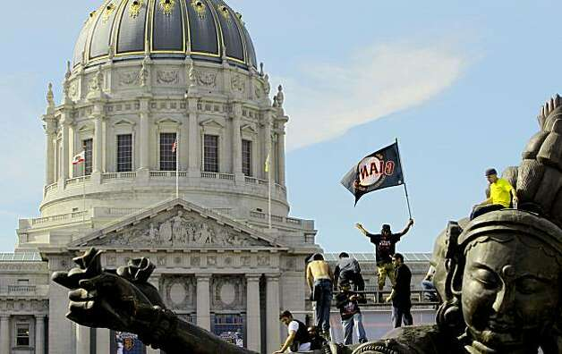 Fans gather at Civiv Center Plaza for the giants rally, climbing atop the 26-foot tall work by Chinese artist Zhang Huan, as the City of San Francisco celebrates the World Series Champion Giants with a parade down Market Street, on Wednesday Nov. 3, 2010 in San Francisco, Calif. Photo: Michael Macor, San Francisco Chronicle