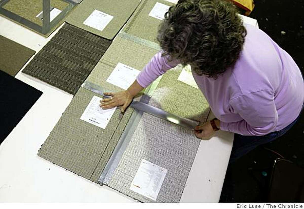 Director Kenan Shapero at SCRAP demonstrates recycling donations of carpet samples into a runner utilizing duct tape photographed in San Francisco on Tuesday, March 10, 2009.