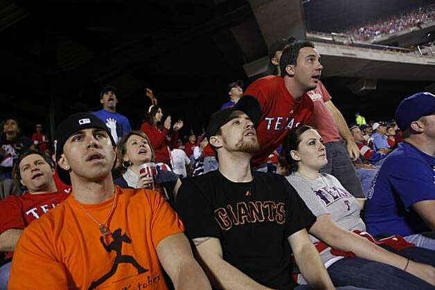 San Francisco Giants fans Patrick Vaughan (left) and William Johnson, who are both originally from San Francisco and currently live in Austin, Texas, watch the top of the third inning of Game 5 of the World Series at Rangers Ballpark on Monday. Photo: Lea Suzuki, San Francisco Chronicle