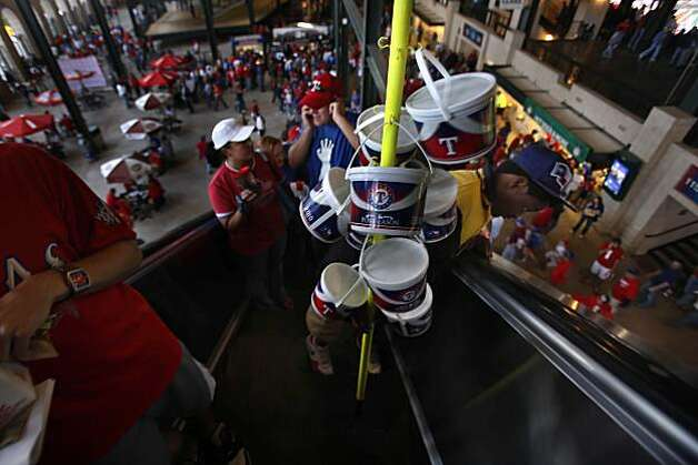Trey Redic (right), County Fair vendor, surveys the crowd below as he rides an escalator before Game 5 of the World Series at Rangers Ballpark on Monday. Photo: Lea Suzuki, San Francisco Chronicle