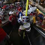 Trey Redic (right), County Fair vendor, surveys the crowd below as he rides an escalator before Game 5 of the World Series at Rangers Ballpark on Monday.