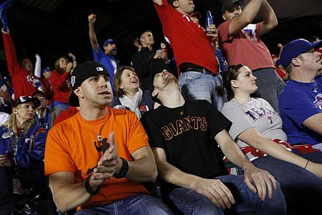 San Francisco Giants fans Patrick Vaughan (left) and William Johnson, who are both originally from San Francisco and currently live in Austin, Texas, react at the end of the top of the third inning at Rangers Ballpark for Game 5 of the World Series on Monday. Photo: Lea Suzuki, San Francisco Chronicle