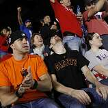 San Francisco Giants fans Patrick Vaughan (left) and William Johnson, who are both originally from San Francisco and currently live in Austin, Texas, react at the end of the top of the third inning at Rangers Ballpark for Game 5 of the World Series on Monday.