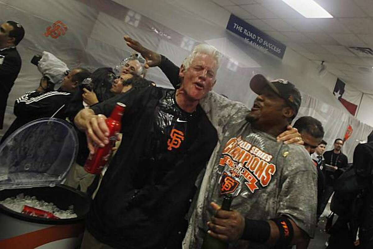 San Francisco Giants managing general partner William Neukom (l to r) and San Francisco Giants Juan Uribe (5) celebrate in the Visiting Clubhouse at Rangers Ballpark after the San Francisco Giants win Game 5 of the World Series over the Texas Rangers 3-1 on Monday November 1, 2010 in Arlington, Texas.