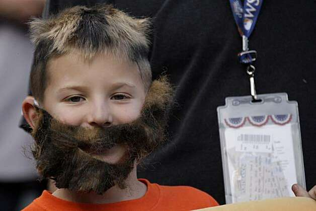 Giants fan Oliver Chessen, 9, of San Francisco decorates his face with a beard while watching the Giants work out before Game 5 of the World Series at Rangers Ballpark on Monday. Photo: Lea Suzuki, San Francisco Chronicle