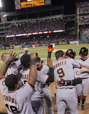 Edgar Renteria gets a hug from Pat Burrell after hitting a three-run home run in the seventh inning of Game 5 of the World Series against the Texas Rangers on Monday. Photo: Michael Macor, San Francisco Chronicle