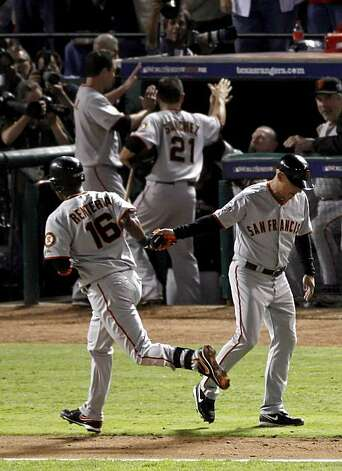 San Francisco Giants shortstop Edgar Renteria is congratulated by third base coach Tim Flannery as Renteria rounds third base after hitting a three-run home run in Game 5 of the World Series against the Texas Rangers on Monday. Photo: Carlos Avila Gonzalez, San Francisco Chronicle