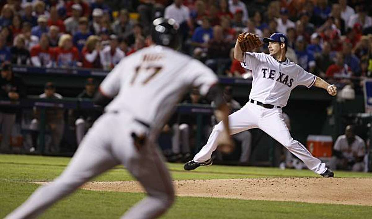 Texas Rangers starting pitcher Cliff Lee delivers a pitch as Aubrey Huff takes a lead in the fifth inning of Game 5 of the World Series on Monday.