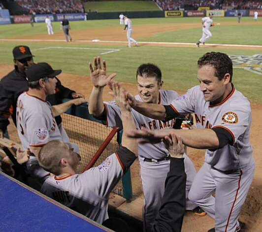 Aubrey Huff, Freddy Sanchez and Pat Burrell celebrate as Edgar Renteria rounds third base after hitting a three-run home run in the seventh inning of Game 5 of the World Series against the Texas Rangers on Monday. Photo: Michael Macor, San Francisco Chronicle