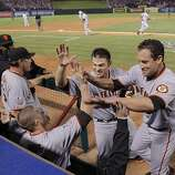 Aubrey Huff, Freddy Sanchez and Pat Burrell celebrate as Edgar Renteria rounds third base after hitting a three-run home run in the seventh inning of Game 5 of the World Series against the Texas Rangers on Monday.