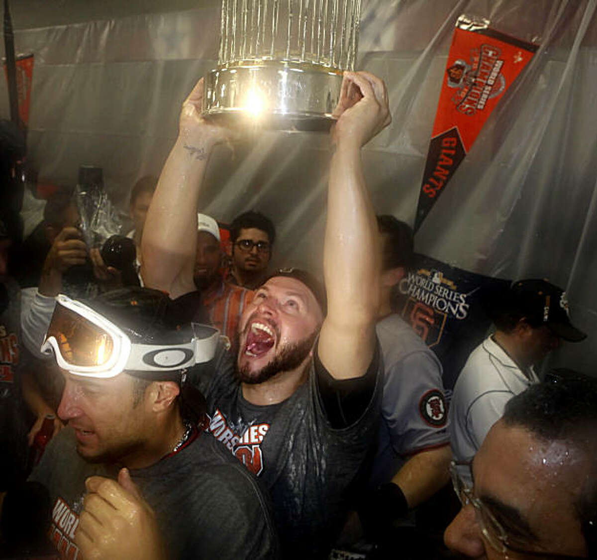 San Francisco Giants' Cody Ross (13) lifts the 2010 World Series Championship trophy over his head in the Visiting Clubhouse at Rangers Ballpark after the San Francisco Giants win Game 5 of the World Series over the Texas Rangers 3-1 on Monday November 1, 2010 in Arlington, Texas.