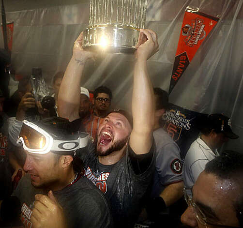 San Francisco Giants' Cody Ross (13) lifts the 2010 World Series Championship trophy over his head in the Visiting Clubhouse at Rangers Ballpark after the San Francisco Giants win Game 5 of the World Series over the Texas Rangers 3-1 on Monday November 1, 2010 in Arlington, Texas. Photo: Lea Suzuki, San Francisco Chronicle