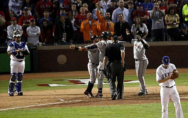 San Francisco Giants shortstop Edgar Renteria is greeted at home plate by Cody Ross and Juan Uribe after Renteria's three-run home run in the seventh inning of Game 5 of the World Series against the Texas Rangers on Monday. Photo: Carlos Avila Gonzalez, San Francisco Chronicle