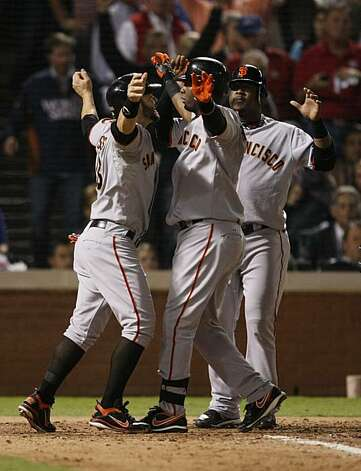 San Francisco Giants Cody Ross and Juan Uribe greet Edgar Renteria as he crosses the plate after hitting a three-run home run in the seventh inning of Game 5 of the World Series against the Texas Rangers on Monday. Photo: Lance Iversen, San Francisco Chronicle