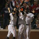 San Francisco Giants Cody Ross and Juan Uribe greet Edgar Renteria as he crosses the plate after hitting a three-run home run in the seventh inning of Game 5 of the World Series against the Texas Rangers on Monday.