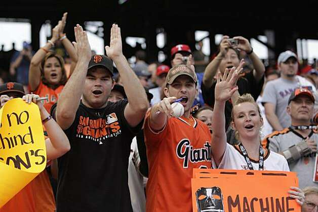 Giants fans cheer for the team during a workout before Game 5 of the World Series against the Texas Rangers at Rangers Ballpark on Monday. Photo: Lea Suzuki, San Francisco Chronicle