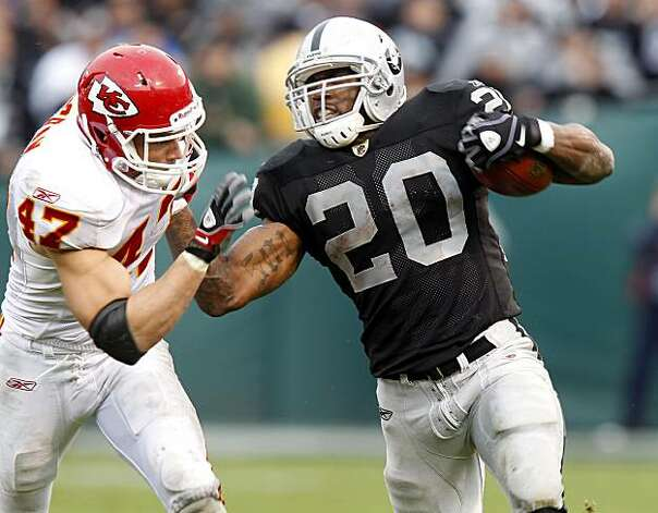 The Raiders' Darren McFadden fights off Chiefs safety Jon McGraw for a big gain in the second half in Oakland on Sunday. Photo: Brant Ward, The Chronicle