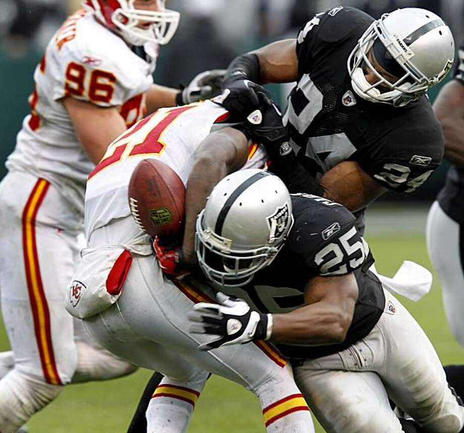 The ball is fumbled by the Chiefs' Javier Arenas in the second half on pressure by the Raiders' Rock Cartwright (25) and Michael Huff in Oakland on Sunday. Photo: Brant Ward, The Chronicle