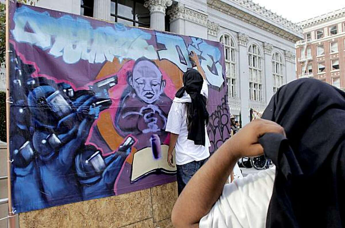"""Artists """"Rapid"""" and """"Base 10"""" create a mural dedicated to Oscar Grant as people gather in front of Oakland City Hall on Friday after a judge sentenced former BART police officer Johannes Mehserle to two years in prison for fatally shooting Grant."""