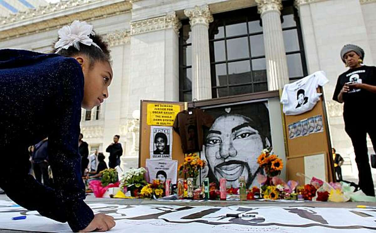 Joyous Miralle DeAsis, 8, of Oakland writes a message on a banner next to a memorial for Oscar Grant as people gather in front of Oakland City Hall on Friday after a judge sentenced former BART police officer Johannes Mehserle to two years in prison for the January 2009 death of Grant.