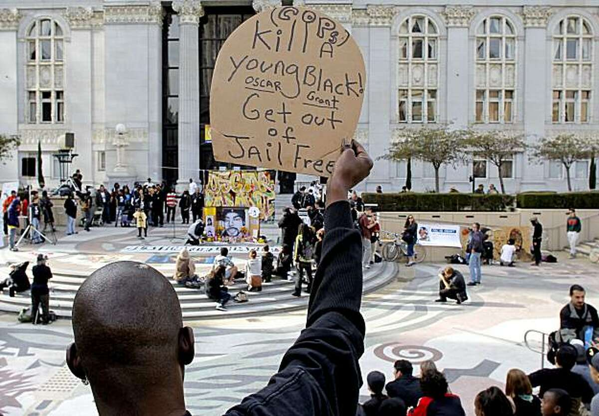 Gregory Nash of Oakland holds a sign as people gather in front of Oakland City Hall on Friday in reaction to former BART police officer Johannes Mehserle's two-year prison sentence for the January 2009 death of Oscar Grant.