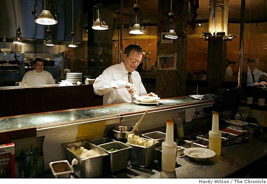 Server Luis Castelero tidies up a plate before bringing it to a table during lunch service at Palio d'Asti restaurant in downtown San Francisco, Calif., on Friday, March 27, 2009. The head of the Golden Gate Restaurant Association said the group would consider dropping its suit fighting the city�s universal health care program if the city would help restaurant owners by instituting a tip credit. Photo: Hardy Wilson, The Chronicle